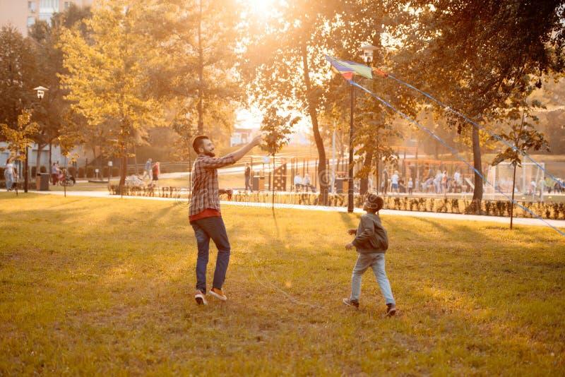 Der Vater und Sohn, die mit einem Drachen in einem Herbst spielen, parken auf a stockbild