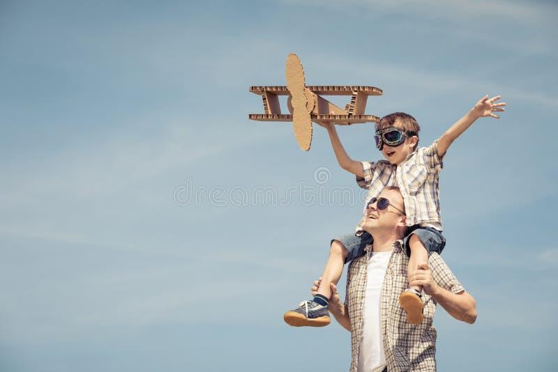 Der Vater und Sohn, die mit Pappe spielen, spielen Flugzeug im Park a lizenzfreie stockfotografie