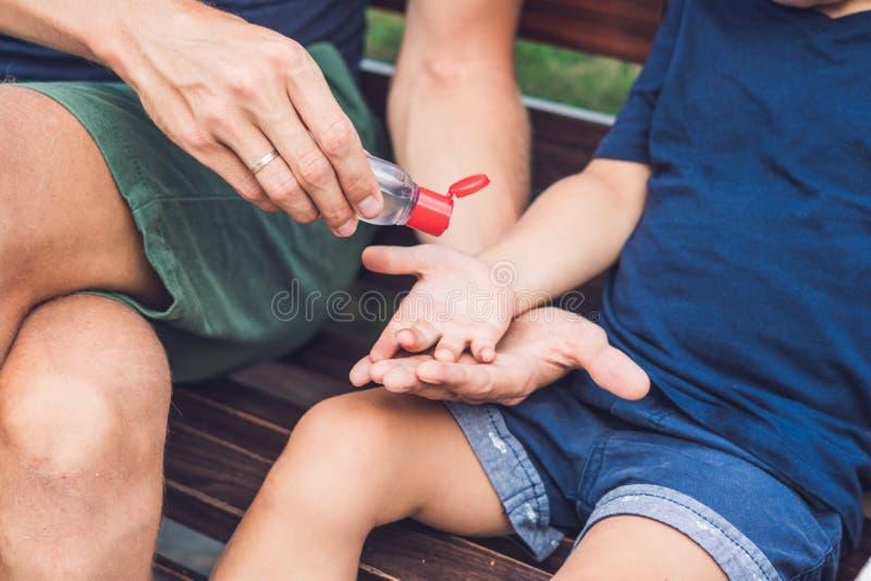 Der Vater und Sohn, die Wäsche verwenden, übergeben Desinfizierergel-Pumpenzufuhr stockfoto