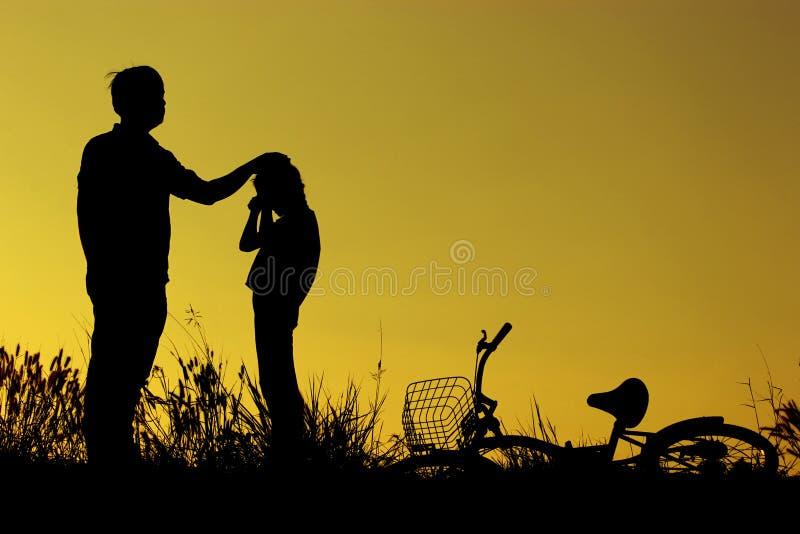 Der Vater und Tochter, die Spaßreitfahrrad bei Sonnenuntergang, aktiver Familiensport, aktive Kinder haben, tragen, asiatisches K lizenzfreies stockbild