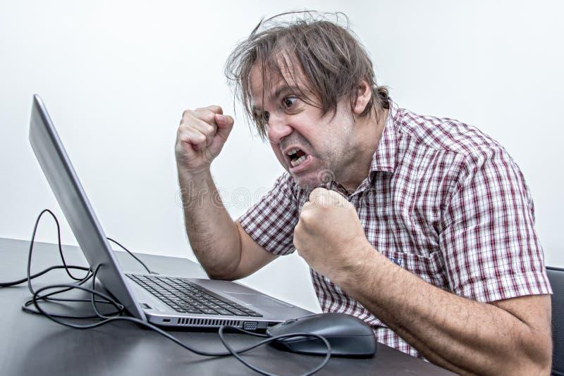 Der verärgerte Benutzer ist zum Laptop schreiend stockfoto