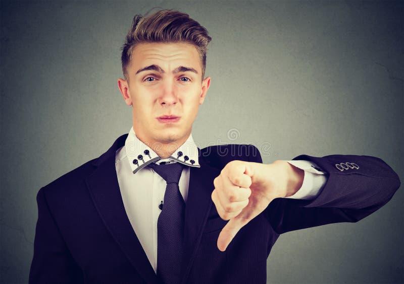 Der verärgerte enttäuschte junge Geschäftsmann, der Daumen unterzeichnen zeigt unten, in der Missbilligung lizenzfreie stockbilder