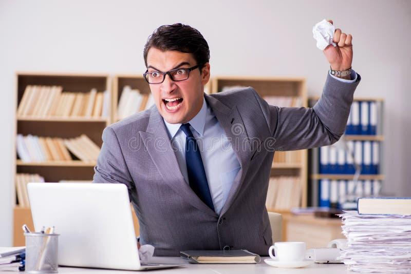 Der verärgerte Geschäftsmann, der im Büro arbeitet stockfotos