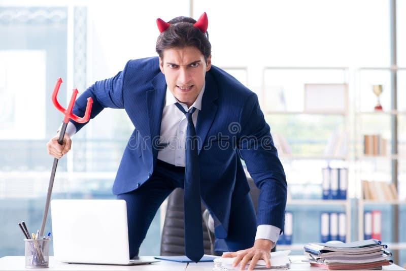 Der verärgerte Geschäftsmann des Teufels im Büro stockfotografie