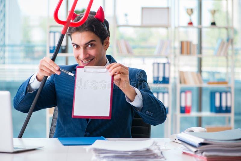 Der verärgerte Geschäftsmann des Teufels im Büro lizenzfreie stockbilder