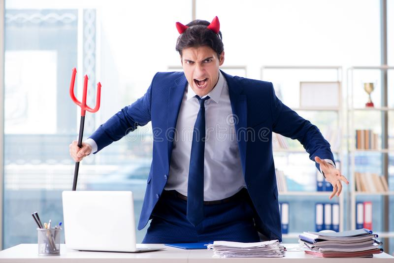 Der verärgerte Geschäftsmann des Teufels im Büro stockfoto
