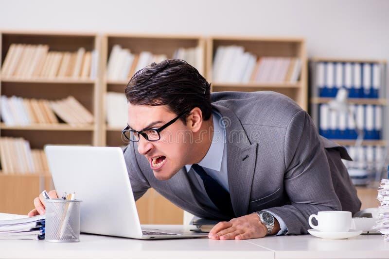 Der verärgerte Geschäftsmann mit zu vieler Arbeit im Büro lizenzfreies stockfoto
