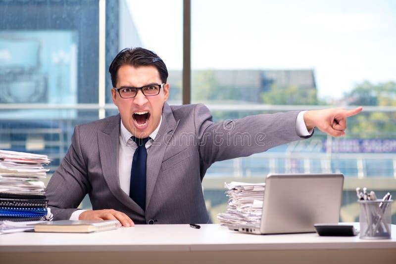 Der verärgerte Geschäftsmann mit zu vieler Arbeit im Büro stockfotografie