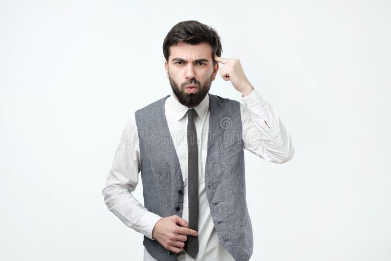 Der verärgerte wütende junge Mann, der mit seinem Finger gegen das Tempelbitten gestikuliert, sind Sie verrückt stockbilder