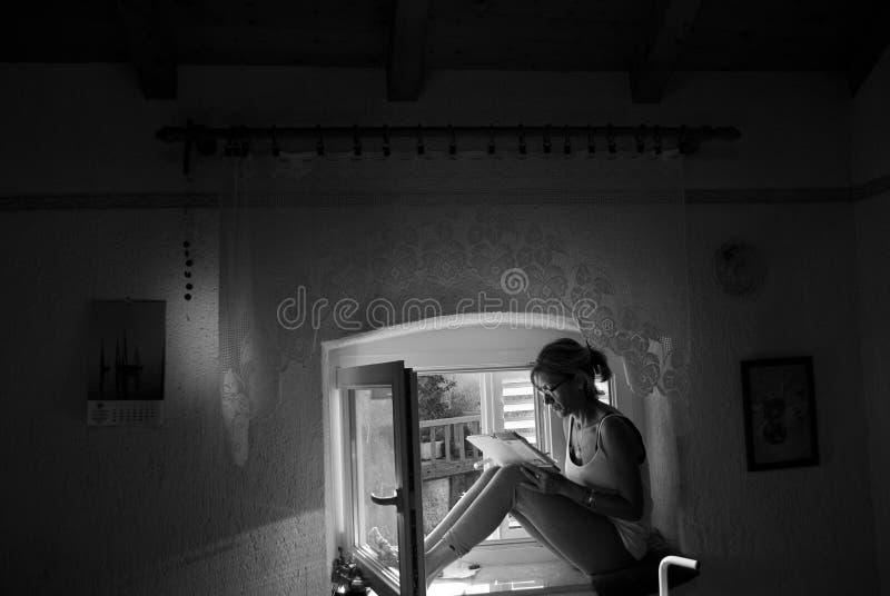 Der Verfasser, der ihre Anmerkungen sitzen auf dem Fenster neuliest lizenzfreie stockfotografie