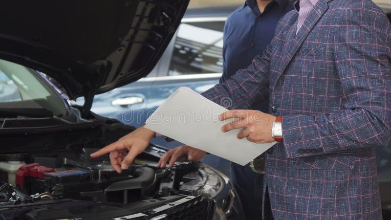 Der Verkäufer beschreibt die Eigenschaften des Autos lizenzfreies stockfoto