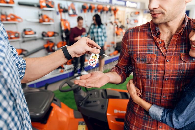 Der Verkäufer gibt jungen Kerl und dem Mädchen die Schlüssel lizenzfreies stockfoto