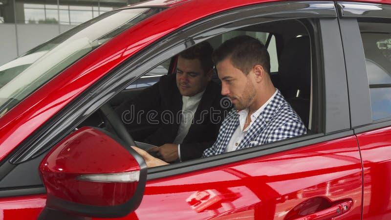 Der Verkäufer und der Käufer sitzen innerhalb des Neuwagens stockfotos