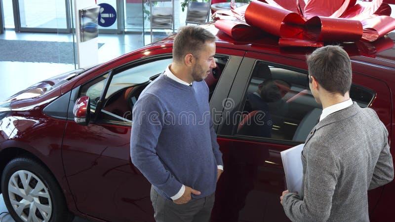 Der Verkäufer von Autos sagt dem Käufer den Eigenschaften des Autos lizenzfreie stockfotos