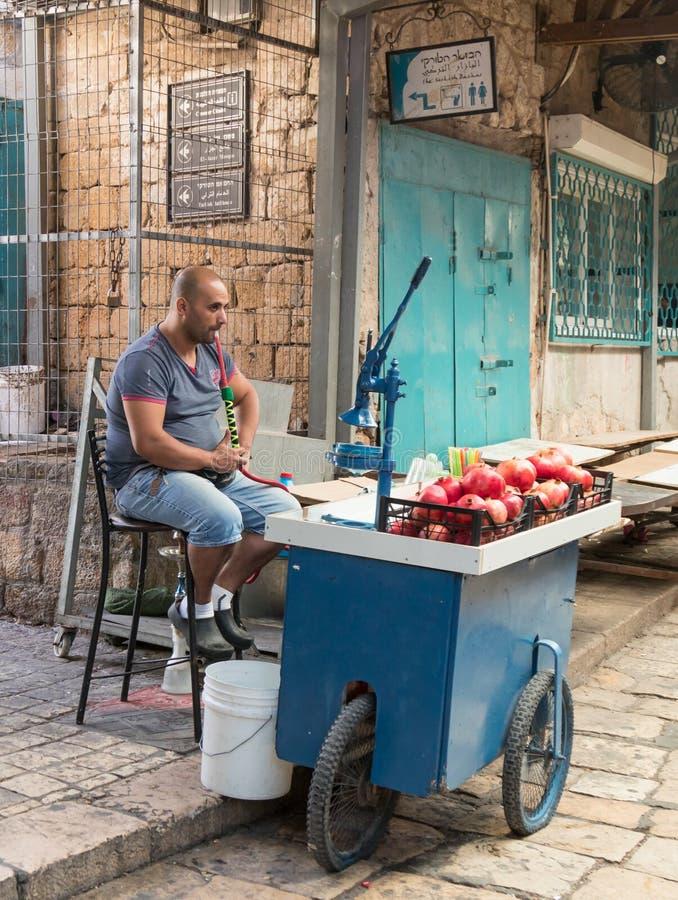 Der Verkäufer von frisch zusammengedrückten Säften sitzt und raucht nargila in Erwartung der Käufer auf dem Markt in der alten St lizenzfreie stockfotografie