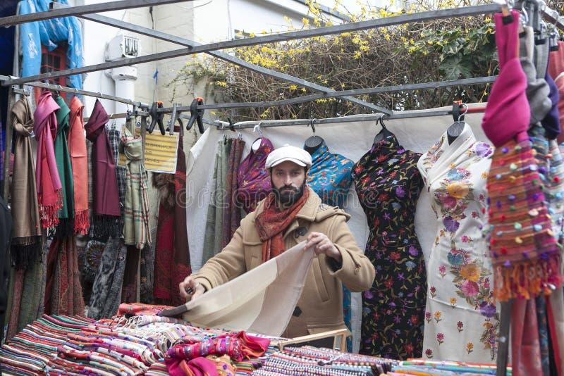 Der Verkäufer von Schals auf Portobello-Straße gegen einen Hintergrund von mehrfarbigen indischen Schals lizenzfreie stockfotos
