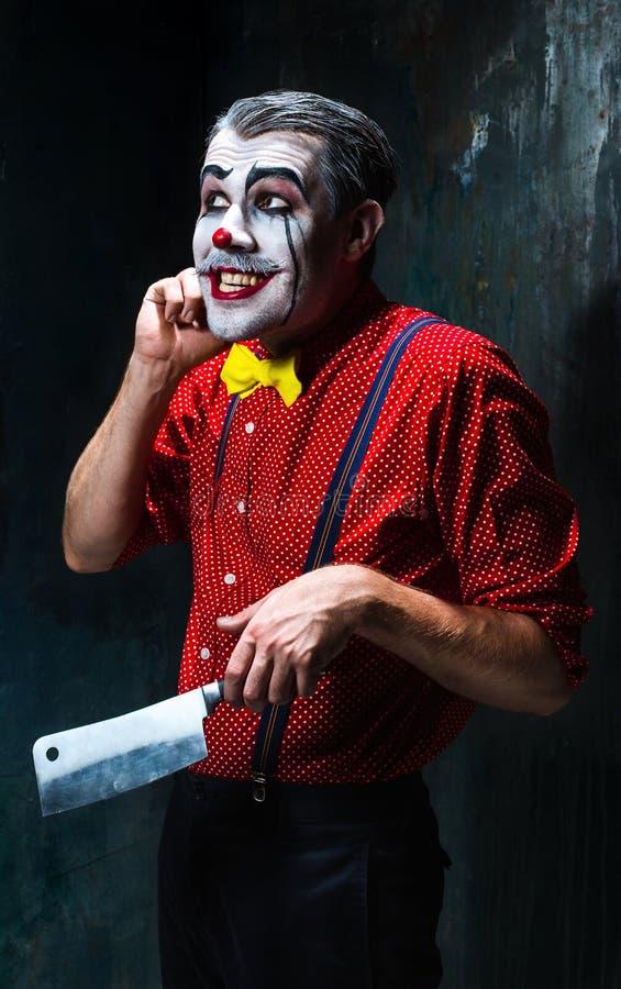 Der verrückte Clown, der ein Messer auf dack hält Ein grimmiger Minireaper, der eine Sense anhält, steht auf einem Kalendertag, d stockfoto