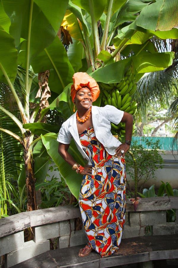 Der vertikale volle K?rper einer frohen Afroamerikanerfrau, die ein helles buntes Nationalkost?m tr?gt, wirft im Garten auf stockfoto