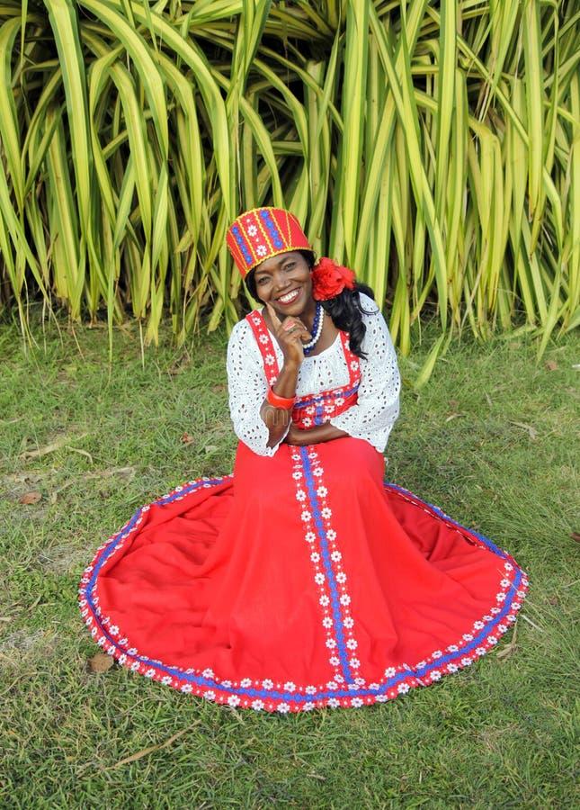 Der vertikale volle K?rper einer frohen Afroamerikanerfrau in einem hellen bunten nationalen russischen Kleid lizenzfreie stockfotos