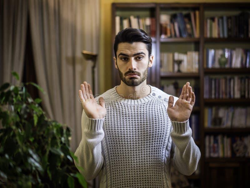 Der verwirrte oder zweifelhafte junge Mann, der mit Palmen zuckt, öffnen sich stockbild