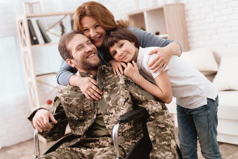 Der Veteran in einem Rollstuhl kam von der Armee zurück Ein Mann in der Uniform in einem Rollstuhl mit seiner Familie stockfotos