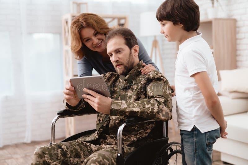 Der Veteran in einem Rollstuhl kam von der Armee zurück Ein Mann in der Uniform in einem Rollstuhl mit seiner Familie lizenzfreie stockfotos