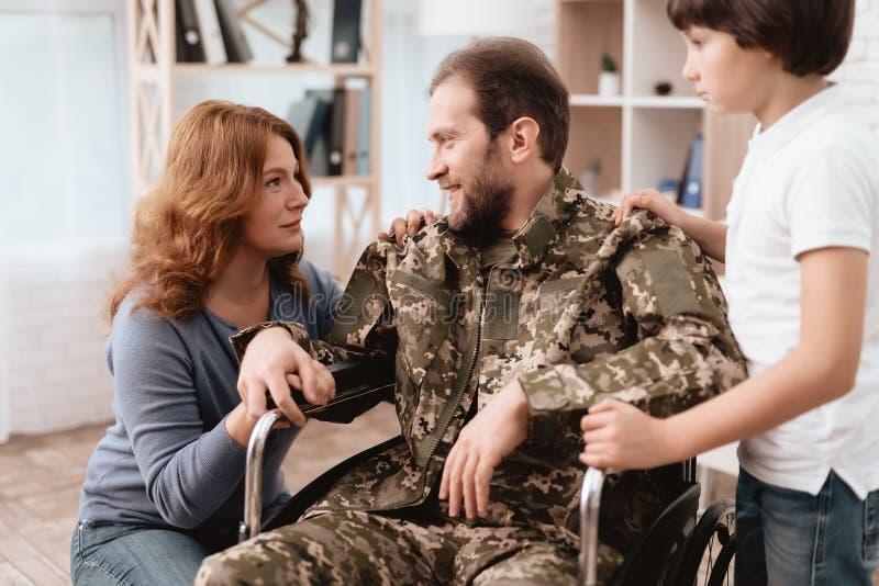 Der Veteran in einem Rollstuhl kam von der Armee zurück Ein Mann in der Uniform in einem Rollstuhl mit seiner Familie stockbilder