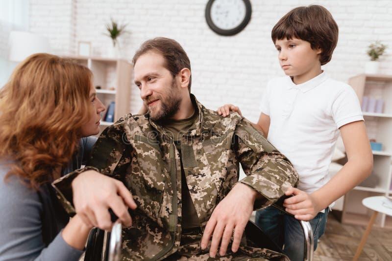 Der Veteran in einem Rollstuhl kam von der Armee zurück Ein Mann in der Uniform in einem Rollstuhl mit seiner Familie lizenzfreie stockbilder