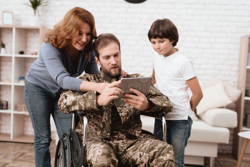 Der Veteran in einem Rollstuhl kam von der Armee zurück Ein Mann in der Uniform in einem Rollstuhl mit seiner Familie lizenzfreie stockfotografie