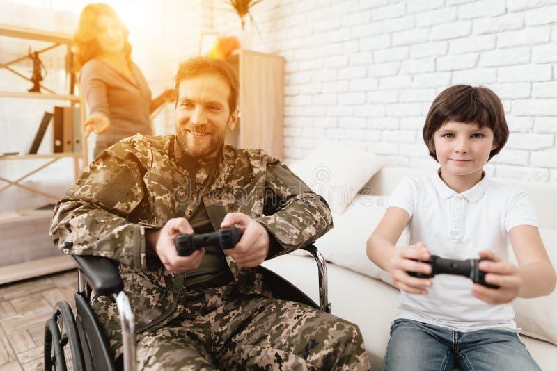 Der Veteran in einem Rollstuhl kam von der Armee zurück Ein Mann in der Uniform in einem Rollstuhl mit seiner Familie stockfoto