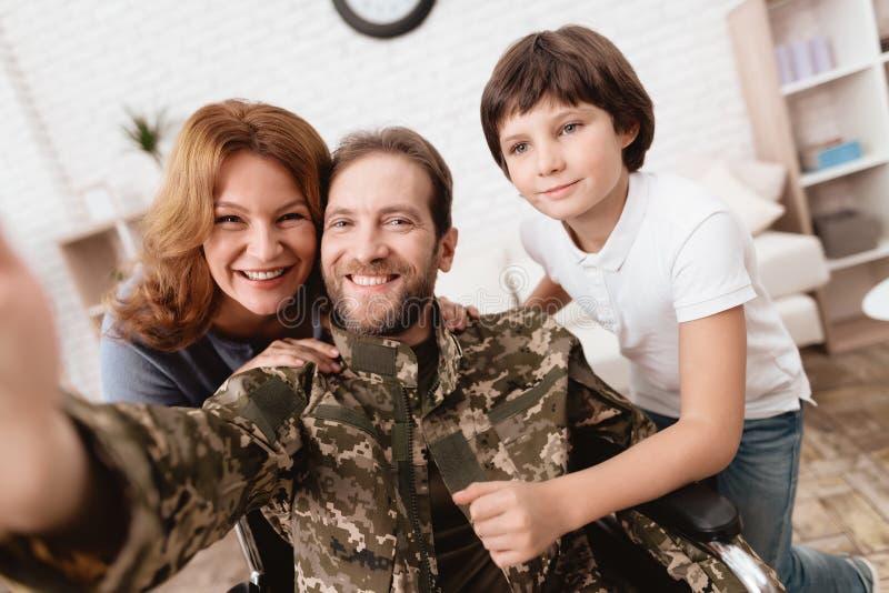 Der Veteran in einem Rollstuhl kam von der Armee zurück Ein Mann in der Uniform in einem Rollstuhl mit seiner Familie stockbild