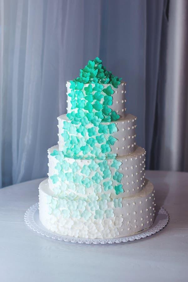 Der vier-abgestufte Kuchen der schönen Haupthochzeit, der mit Türkis verziert wird, blüht auf weißer Tabelle lizenzfreie stockfotos