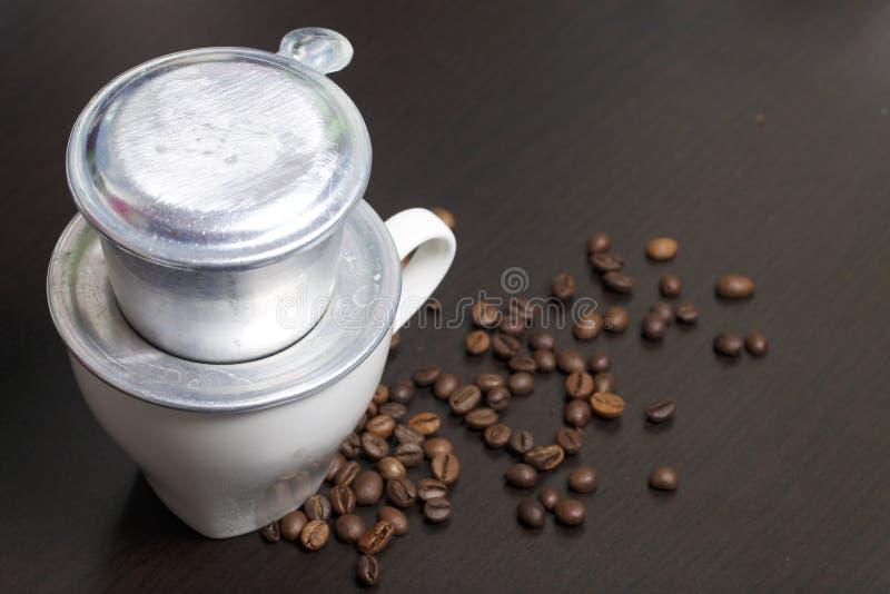 Der vietnamesische Brauer für Kaffee in zusammengebauter Form steht auf einer weißen Schale Folgende zerstreute Kaffeebohnen stockfoto