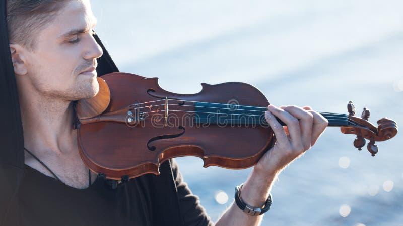 Der Violinist, der eine Violine, junger Mann spielt, spielt an stockfotografie