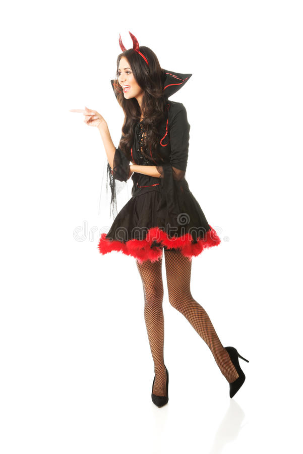 Der in voller Länge tragender Teufel Frau kleidet das Zeigen nach links lizenzfreies stockbild