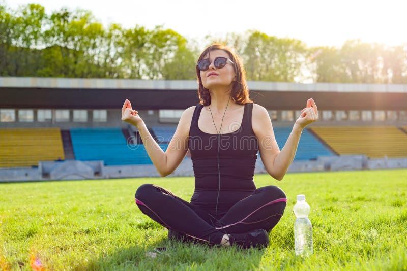 Der von mittlerem Alter übendes Yoga Frau im Stadion lizenzfreie stockbilder