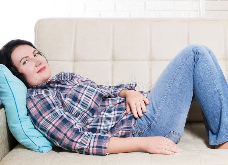 Der von mittlerem Alter das lächelnde Lügen ruhigen ruhigen Frau auf Raummädchen der Couch zu Hause hat Bruch nach der Arbeit, od stockbild