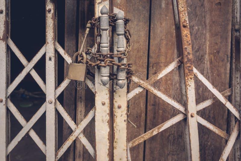 Der Vorderansichtaltgoldstahlriegel und die schädigende und verrostete Stahltür stockbild