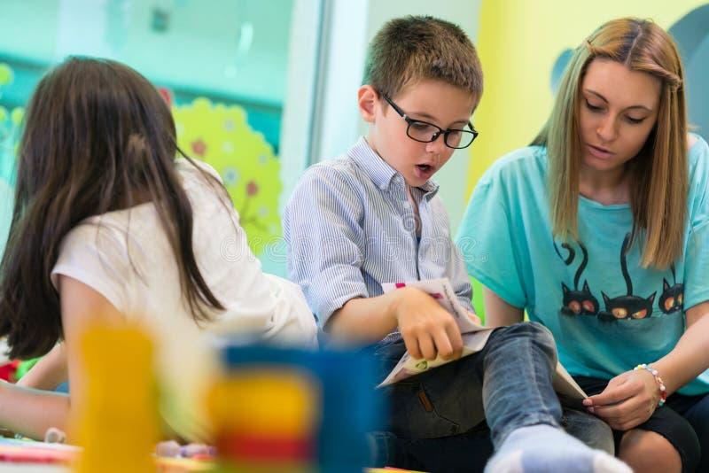 Der Vorschule- Junge, der lernt zu lesen, half durch einen Kindergärtnerinassistenten stockfotografie
