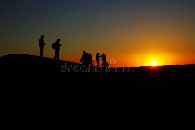 Der Wüstensonnenuntergang besprüht auf den Leuten stockbild
