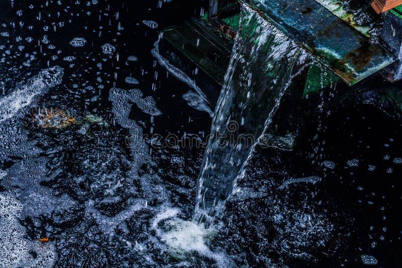 Der Wasserfall fließt von der überfließenden Mündung stockfoto