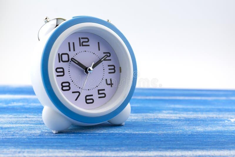 Der Wecker ist auf einem gemalten blauen Brett stockfotos