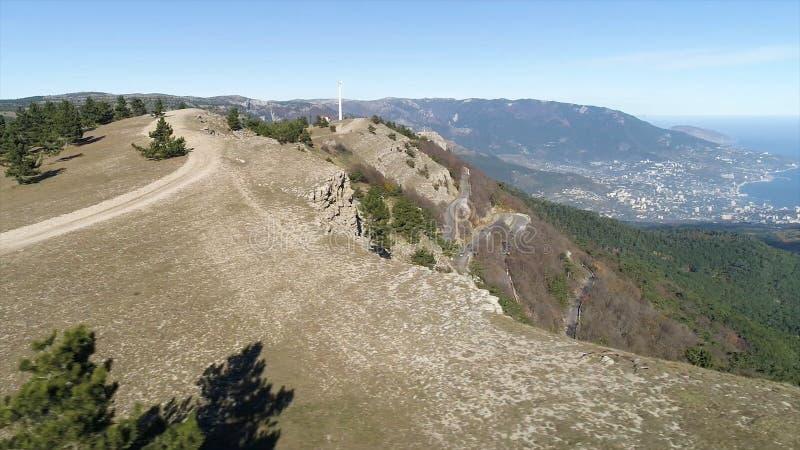 Der Weg auf dem Hügel mit Fichten nahe steiler Steigung mit einem Tal und Küstenstadt auf Hintergrund des blauen Himmels schuß ae stockbild