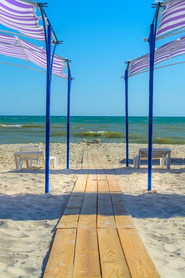 Der Weg von hölzernen Planken auf dem Strand geht zum Meer lizenzfreies stockfoto
