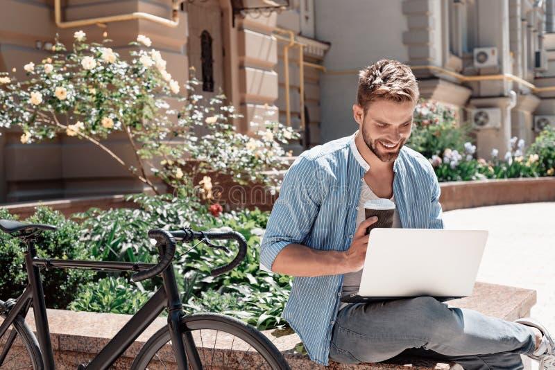 Der Weg zum Erfolg ist, enorme Maßnahmen zu ergreifen Junger lächelnder Mann, der im Park, seinen Laptop und eine Schale von halt stockfotografie