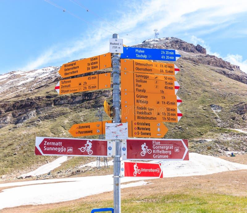 Der Wegweiser, der auf Deutsch geschrieben wird, sagt verschiedenen Wanderwegen, Zermatt, die Schweiz Blumenweg ist blumen schlep stockfotografie