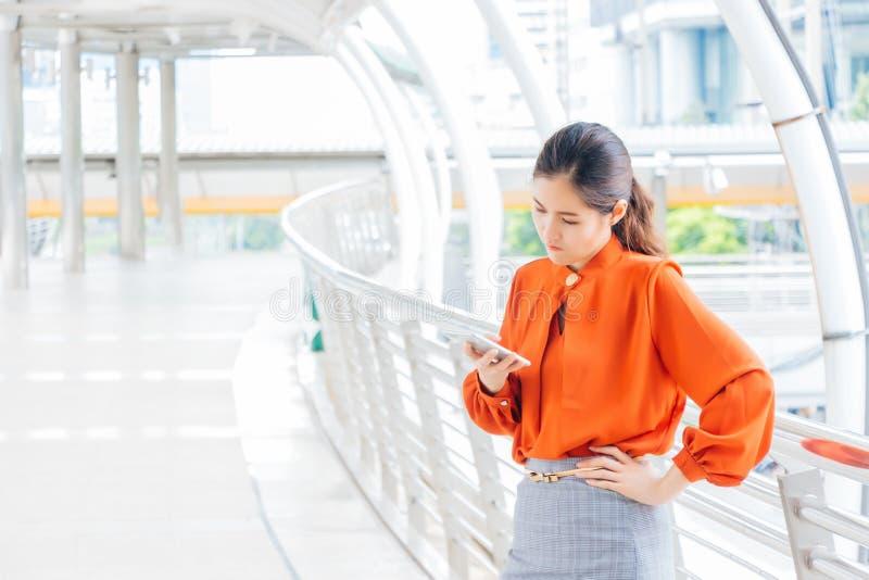 Der weibliche Büroangestellte wird frustriert, dass der Freund spät kommt Es gibt ein hohes Gebäude im im Freien stockbilder