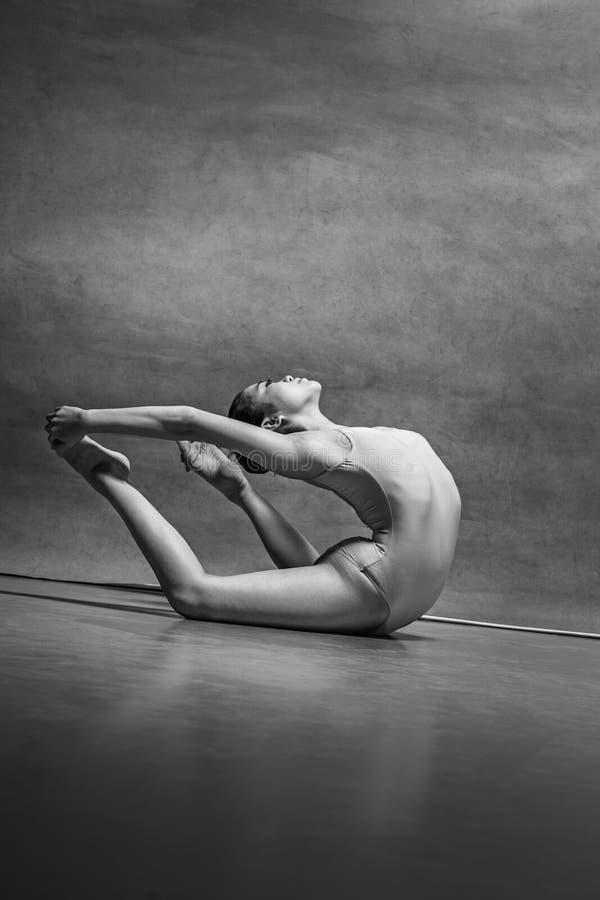 Der weibliche Balletttänzer, der über grauem Hintergrund aufwirft lizenzfreies stockfoto