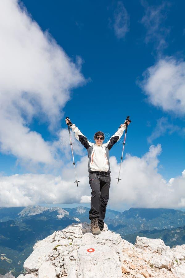 Der weibliche Bergsteiger, der ein erfolgreiches feiert, steigen auf stockbild