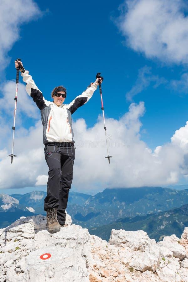 Der weibliche Bergsteiger, der ein erfolgreiches feiert, steigen auf stockbilder